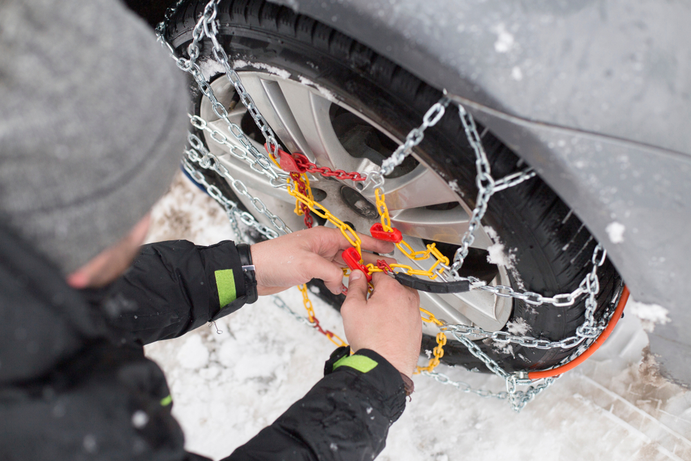 Person installing snow chains on their car tire