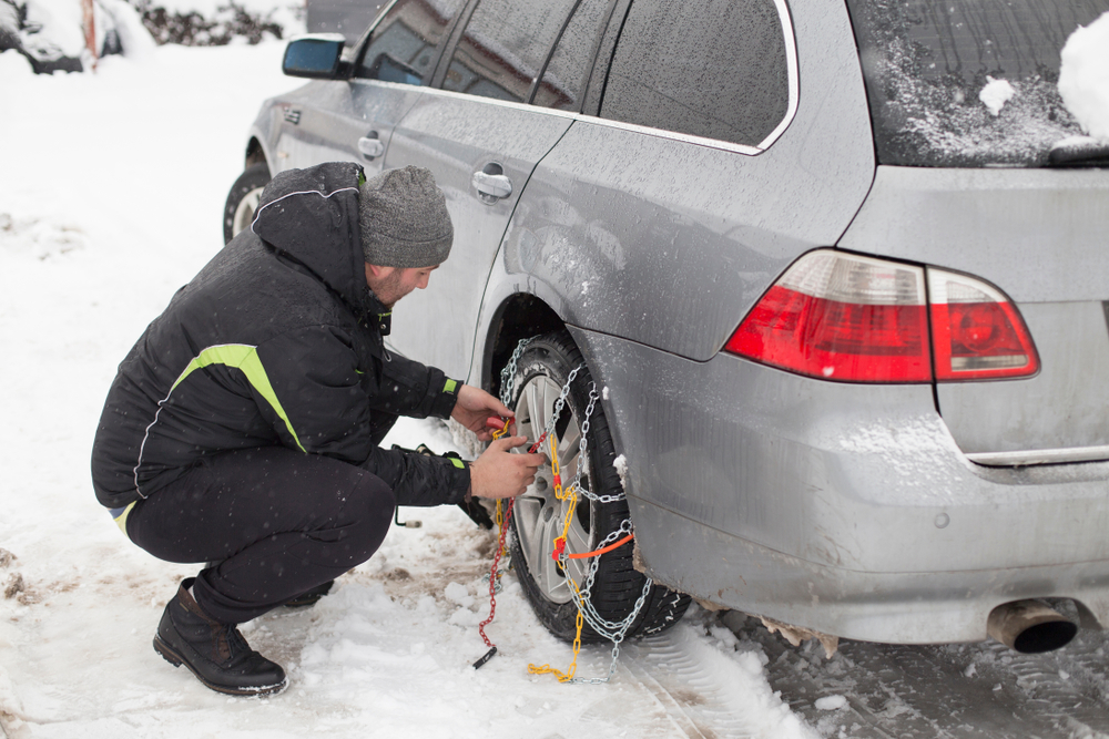 Person installing snow chains on car