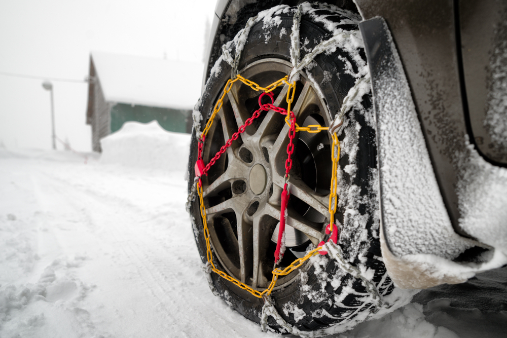 snow chains on tire on snow covered road