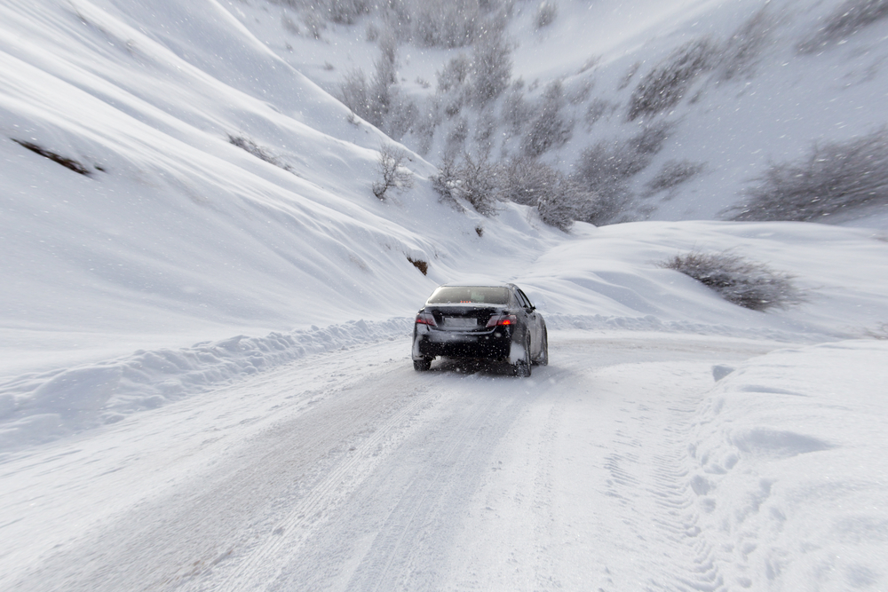 car driving on snow covered road in mountains